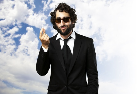 portrait of young business man gesturing money against a cloudy sky background Stock Photo - 12105265