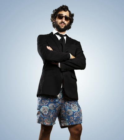 contradiction: portrait of young business man wearing swimsuit against a blue background Stock Photo