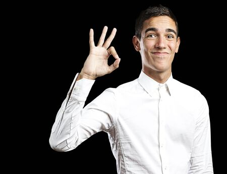 Portrait of a handsome young man smiling and gesturing okay sign against black background photo