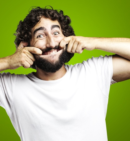 portrait of young man pulling his mouth smiling over white background Stock Photo - 12105439