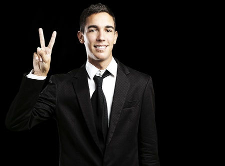 portrait of handsome young man doing good symbol against a black background photo