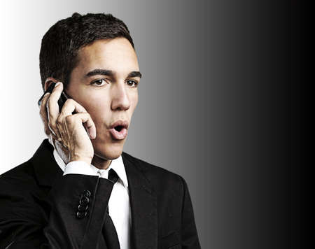 portrait of handsome young man talking on mobile against a black background photo