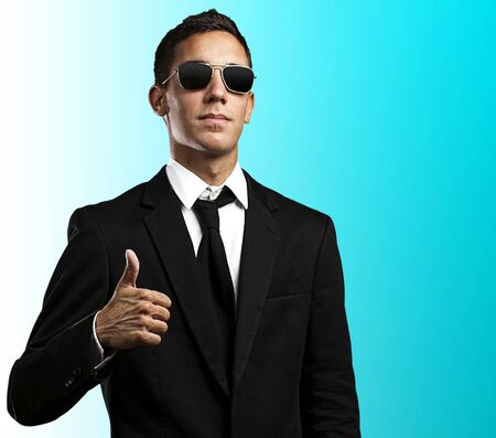 portrait of a serius business man doing approve gesture over blue background Stock Photo - 12105480