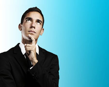 portrait of pensive young business man against a blue background  photo