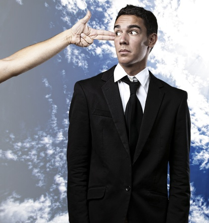 man gesturing gun pointing a business man against a cloudy sky background photo