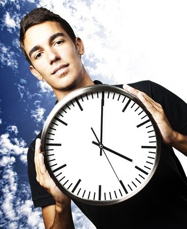 portrait of young man holding a clock with his hands against a cloudy sky background Stock Photo - 12105409
