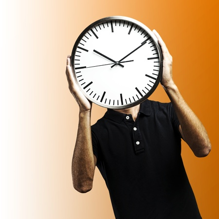 young man covering his face with a clock over orange background Stock Photo - 12100558