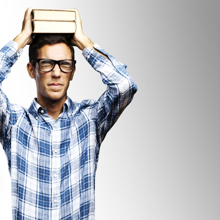 portrait of young man with glasses holding books on his head over grey background photo