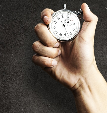 hand holding stopwatch against a grunge background photo