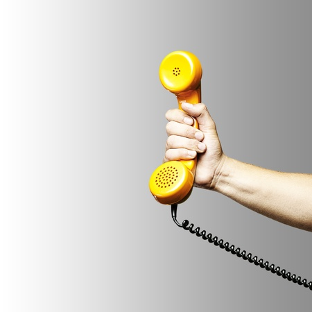 hand holding a yellow vintage telephone over grey background photo
