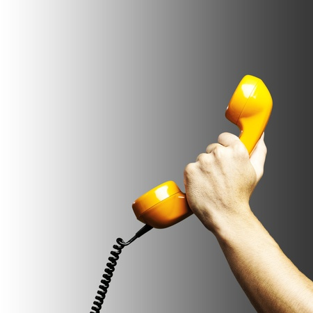 Hand holding vintage telephone receiver isolated over grey background photo