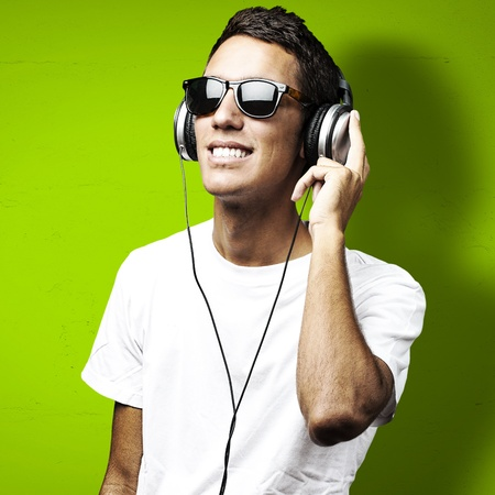 portrait of young man with sunglasses playing to music on a green background photo