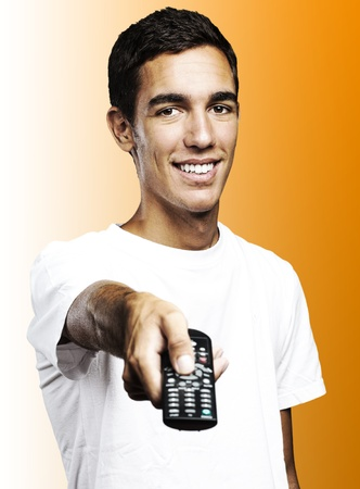 changing channels: young man smiling and changing the channel of tv against a orange background