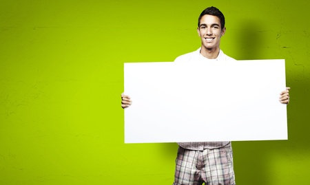 a placard: young man smiling and showing a big banner against a green background