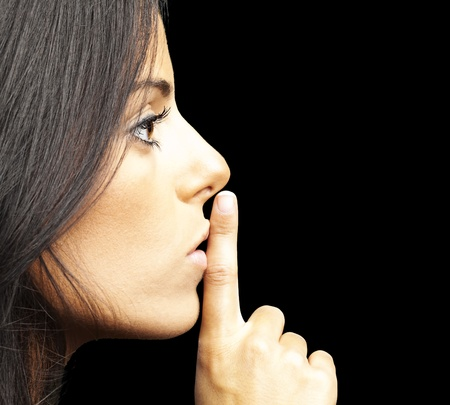 portrait of young woman doing silence sign against a black background Stock Photo - 12105500