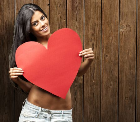 portrait of young woman holding red heart against a wooden wall photo