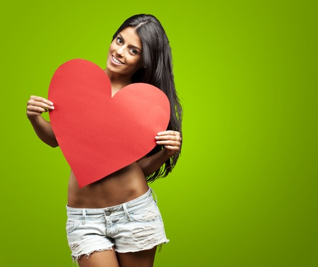 adult valentine: portrait of young woman holding red heart against a green background