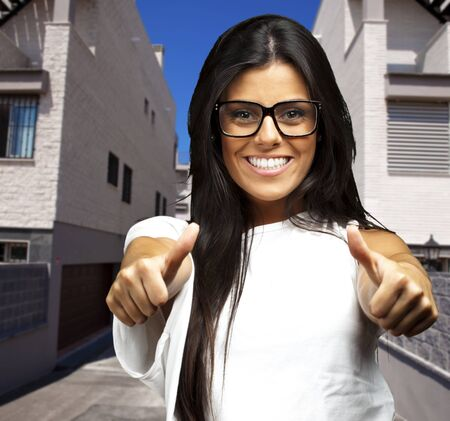 latin girls: portrait of a pretty young woman doing good symbol against a building