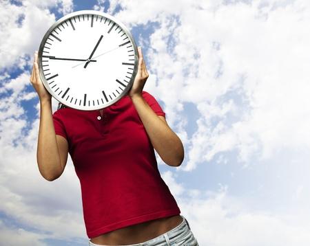 woman clock: mujer con el reloj delante de la cabeza contra un fondo de cielo nublado Foto de archivo