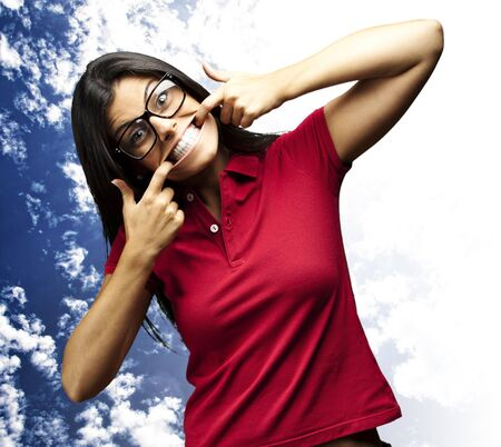 portrait of a happy young woman gesturing with the mouth against a cloudy sky background photo
