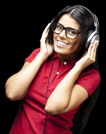 portrait of young woman listening to music against a black background Stock Photo - 12105434