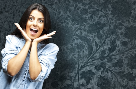portrait of surprised young woman against a vintage wall photo