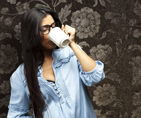 portrait of a pretty young woman drinking coffee on a cup against a vintage wall photo