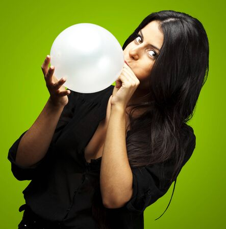 portrait of young woman blowing balloon against a green background photo