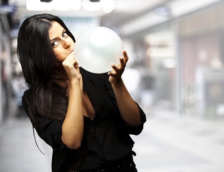 inflating: portrait of young woman blowing balloon at a crowded place
