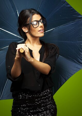 portrait of young woman holding umbrella over green background photo