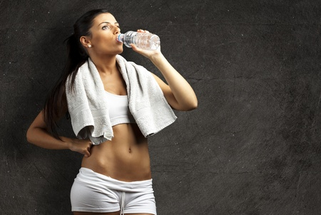 portrait of healthy young woman drinking water against a grunge background photo