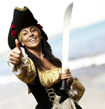 portrait of pirate woman holding a sword and gesturing ok at the beach photo