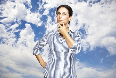 portrait of middle aged woman thinking against a cloudy sky background photo