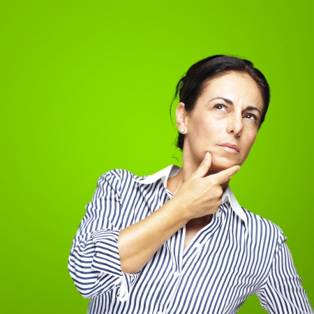 portrait of a middle aged woman thinking against a green background photo
