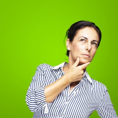 donna pensiero: ritratto di una donna di mezza et� a pensare contro uno sfondo verde