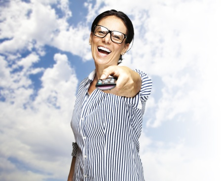 portrait of a middle aged woman using tv control with a cloudy sky as a background photo