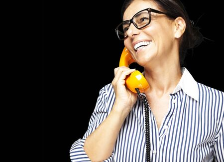 portrait of middle aged woman wearing glasses with vintage telephone on black background Stock Photo - 12105746