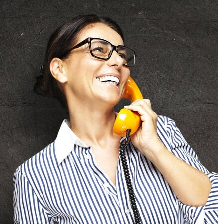 portrait of middle aged woman talking on vintage telephone against a grunge background Stock Photo - 12105493