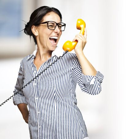 portrait of a middle aged woman talking on vintage telephone indoor photo