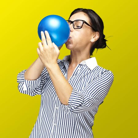 latex girl: portrait of a middle aged woman blowing a balloon against a yellow background Stock Photo