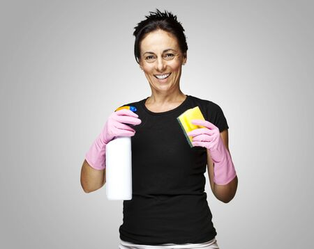 portrait of a middle aged woman with gloves ready to clean over grey background photo