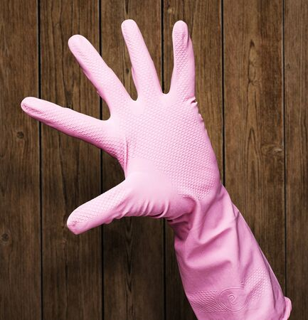 housewife gloves: pink rubber gloves against wooden wall