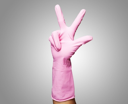 pink gloves of maid gesturing number three against a grey background photo