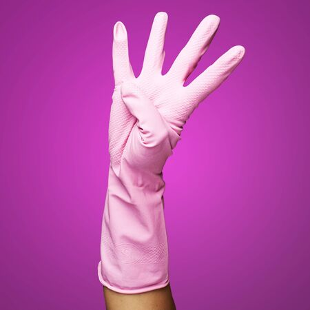 pink gloves of maid gesturing number four against a pink background photo