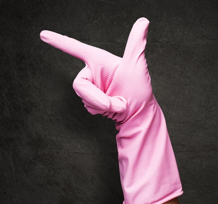pink rubber gloves pointing against a grunge background photo