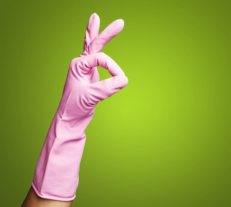 pink rubber gloves gesturing rabbit against a green background Stock Photo