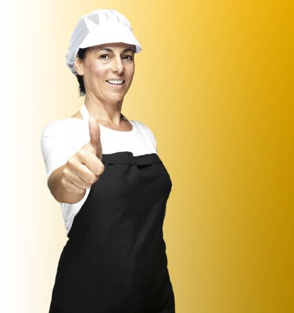 okey: portrait of cook wearing apron and mesh top hat doing okey symbol against yellow background