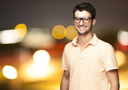 portrait of a young man smiling against a city by night Stock Photo - 12104806