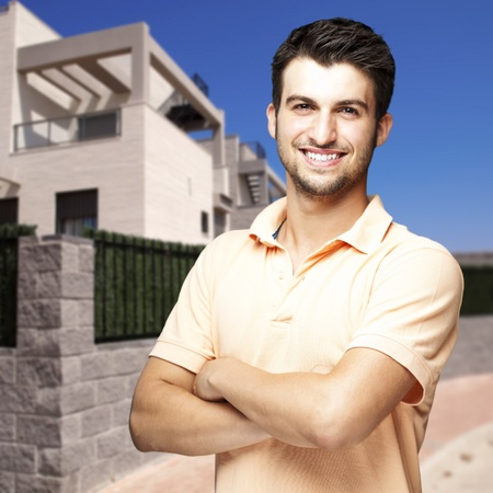 portrait of a young man smiling against a house photo
