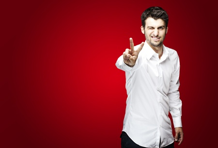 wink: portrait of young man handsome doing good symbol over red background